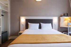 A bed or beds in a room at Hôtel Baldi by Magna Arbor