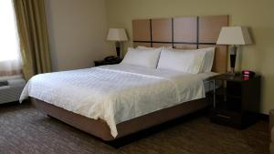 A bed or beds in a room at Candlewood Suites Woodward, an IHG Hotel