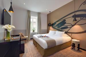 A bed or beds in a room at Hôtel & Spa Jules César Arles - MGallery Hotel Collection