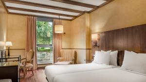 A bed or beds in a room at Hotel Palacio del Carmen, Autograph Collection