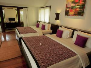 A bed or beds in a room at Tropicana Lanta Resort