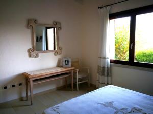 A bed or beds in a room at Punta Falcone Resort