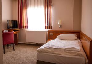 Ein Bett oder Betten in einem Zimmer der Unterkunft Bundt's Hotel & Gartenrestaurant
