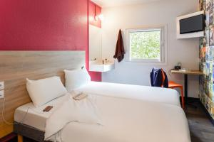A bed or beds in a room at hotelF1 Villeneuve Loubet