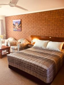 A bed or beds in a room at Colonial Motor Inn Pambula