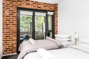 A bed or beds in a room at Byron Butter Factory Apartments