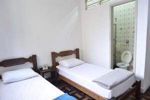 Cama ou camas em um quarto em Mônaco Hotel
