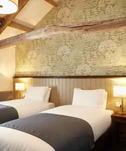 A bed or beds in a room at Kings Head Hotel by Greene King Inns