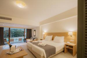 A bed or beds in a room at Corfu Holiday Palace