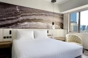 Een bed of bedden in een kamer bij The Park Lane Hong Kong, a Pullman Hotel