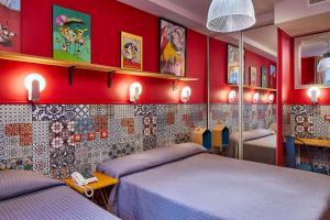 A bed or beds in a room at Hôtel de Roubaix