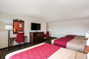 A bed or beds in a room at Rodeway Inn Cedar Rapids