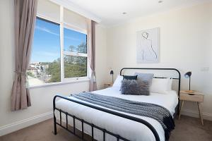 A bed or beds in a room at View Of Manly Pines And Waves From Large Apartment