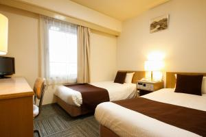 A bed or beds in a room at Shin-Osaka Sunny Stone Hotel