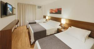 A bed or beds in a room at Premier Copacabana Hotel