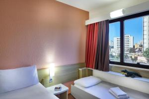 A bed or beds in a room at ibis Taubate