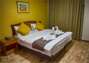 A bed or beds in a room at Shweiki International Hotel