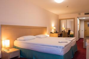 A bed or beds in a room at Riga Islande Hotel with FREE Parking