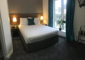 A bed or beds in a room at The Abbey Hotel