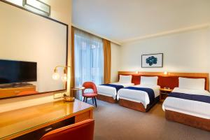 A bed or beds in a room at BEST WESTERN PLUS Travel Inn
