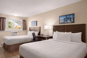 A bed or beds in a room at Travelodge by Wyndham Salmon Arm BC