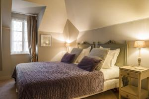 A bed or beds in a room at Hôtel Restaurant Les Ormes, The Originals Relais (Relais du Silence)