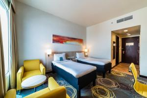 A bed or beds in a room at Ibis Styles Dragon Mart Dubai