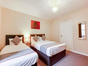 A bed or beds in a room at Lost Guest House Peterhead