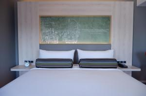 A bed or beds in a room at Aloft Jakarta Wahid Hasyim