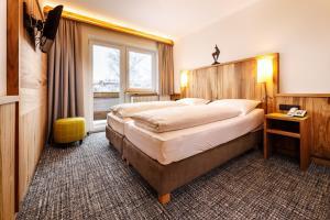 A bed or beds in a room at Hotel Garni Entstrasser