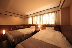 A bed or beds in a room at Hotel Tsubakino