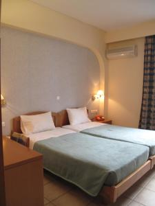 A bed or beds in a room at El Greco Hotel