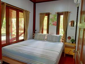 A bed or beds in a room at Baan Moonchan House