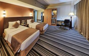 A bed or beds in a room at Pearl Grand Hotel