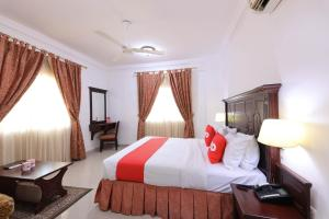 A bed or beds in a room at OYO 125 Manam Sohar Hotel Apartments