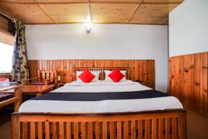 A bed or beds in a room at Capital O 47240 Hotel Blossom Resort