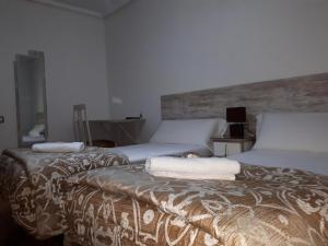 A bed or beds in a room at Pensión Saint Mateo