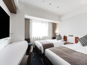 Tempat tidur dalam kamar di HOTEL MYSTAYS Sapporo Station