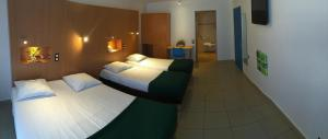 A bed or beds in a room at Karaibes Hotel