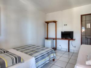 A bed or beds in a room at Pousada Coqueiral