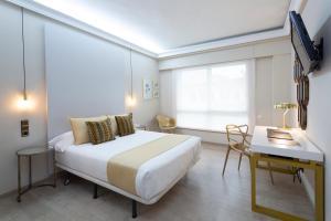 A bed or beds in a room at Hotel Ciudad de Vigo