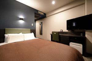 A bed or beds in a room at Kawasaki Daiichi Hotel Mizonokuchi