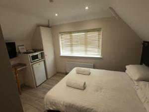 A bed or beds in a room at Debden Guest House