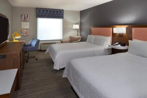 A bed or beds in a room at Hampton Inn & Suites Montreal-Dorval