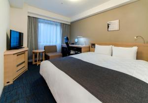 A bed or beds in a room at Daiwa Roynet Hotel Kyoto Shijo Karasuma