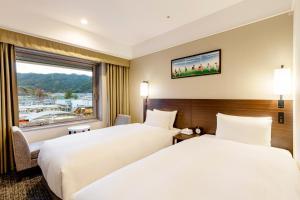 Een bed of bedden in een kamer bij Kyoto Yamashina Hotel Sanraku