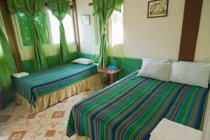 A bed or beds in a room at Zapote Tree Inn