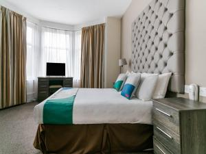 A bed or beds in a room at OYO The Ivory Hotel