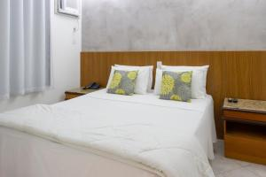 A bed or beds in a room at Ilha Porchat Hotel