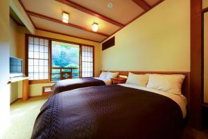 A bed or beds in a room at Yamabiko Ryokan